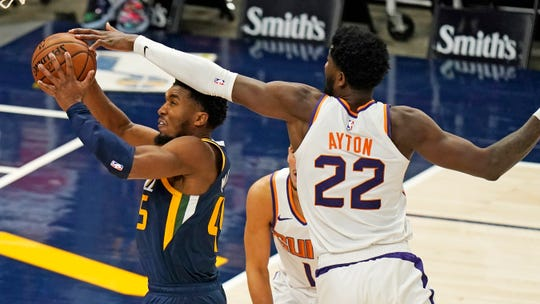 Utah Jazz guard Donovan Mitchell (45) goes to the basket as Phoenix Suns center Deandre Ayton (22) defends during the second half of an NBA basketball game Thursday, Dec. 31, 2020, in Salt Lake City. (AP Photo/Rick Bowmer).