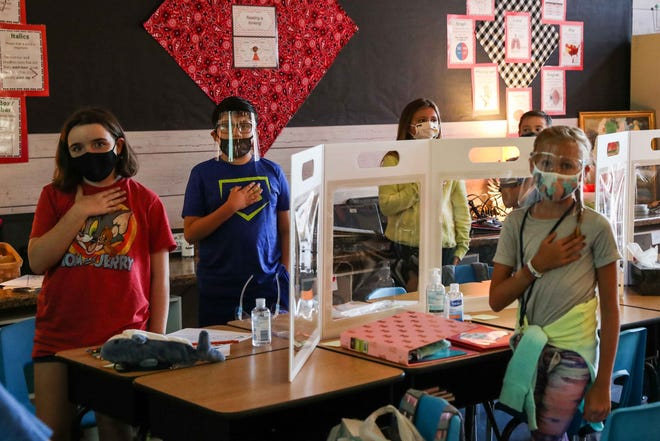 Fourth graders wearing masks and face shields say the Pledge of Allegiance at Jacob's Well Elementary school in Wimberley on the first day of classes in August. State education leaders' pandemic management is expected to be scrutinized during the upcoming legislative session.