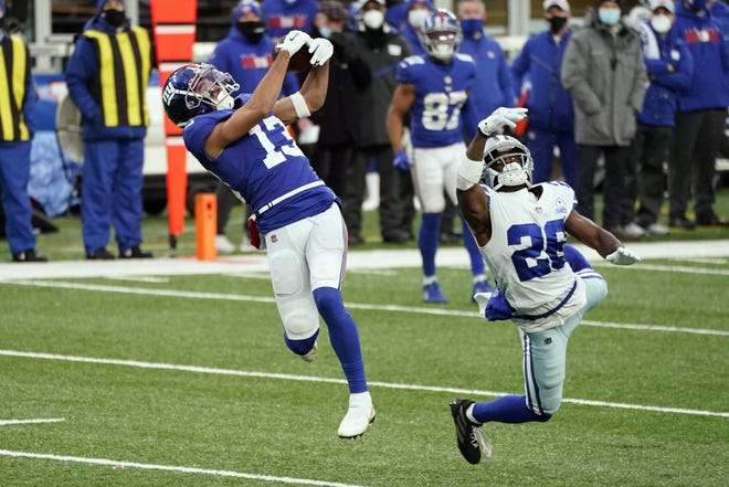 New York Giants' Dante Pettis, left, makes a catch in front of Dallas Cowboys' Xavier Woods during the Giants' 23-19 win Sunday. With the loss, the Cowboys' playoff hopes ended.