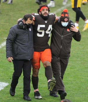 Browns defensive end Olivier Vernon is helped off the field during the fourth quarter against the Pittsburgh Steelers on Sunday. Vernon suffered a ruptured left Achilles tendon and will not play in Sunday's wild-card playoff against the Steelers in Pittsburgh. [Phil Masturzo/Beacon Journal]