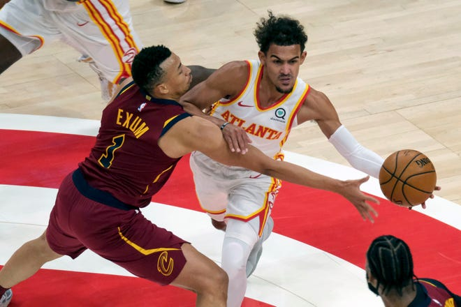 Atlanta Hawks guard Trae Young (11) is fouled by Cleveland Cavaliers guard Dante Exum (1) during the first half of an NBA basketball game on Saturday, Jan. 2, 2021 in Atlanta. (AP Photo/Ben Gray)