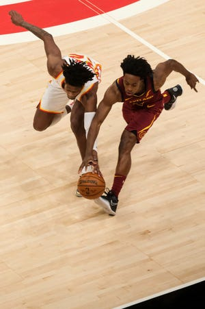 Atlanta Hawks forward Cam Reddish (22) and Cleveland Cavaliers guard Collin Sexton (2) dive for the ball during the first half of an NBA basketball game on Saturday, Jan. 2, 2021, in Atlanta. (AP Photo/Ben Gray)