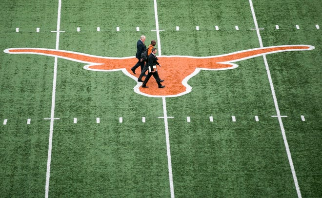 Tom Herman crosses the Longhorns logo at midfield of Royal-Memorial Stadium, flanked by UT athletic director Mike Perrin and UT executive senior athletic director Arthur Johnson as they make their way to Herman's introductory press conference as Texas' new head coach on Nov. 27, 2016.