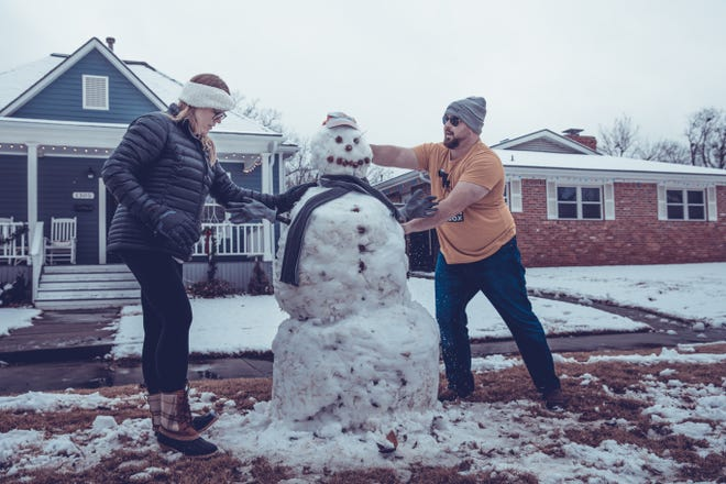 Emily Voelkers and Mike Epps put on the finishing touches of their life-size snow man on Jan 1.