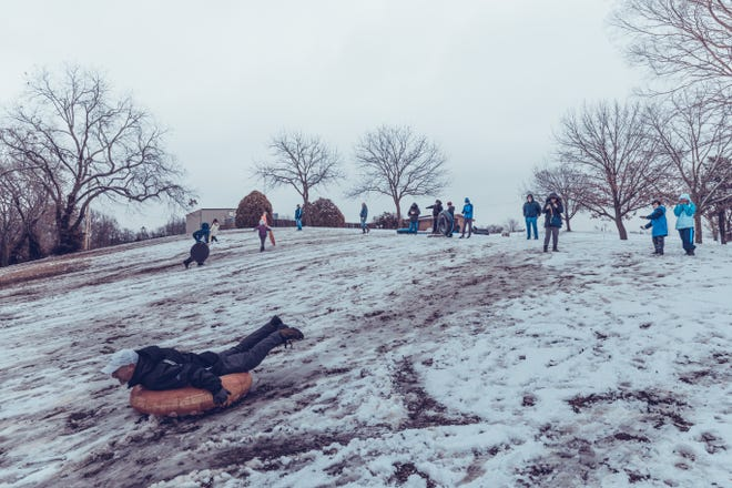 Dennis Waterman takes to the hills as he enjoys the first snow of 2021 with other Bartlesville residents at Sooner Park on Jan. 1.