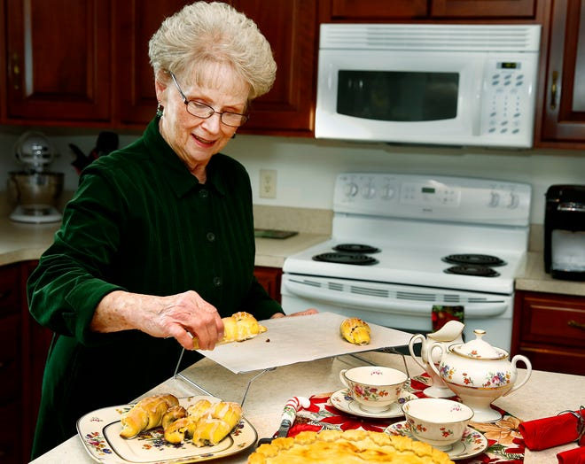 Carol Williams of Wooster arranges coconut butterhorns on a plate.