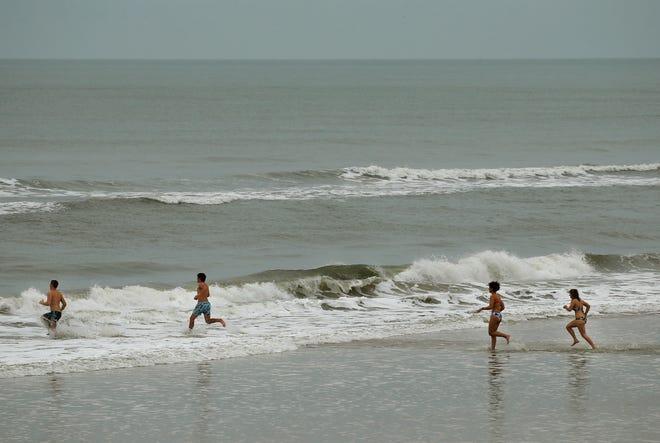 Beachgoers race in the surf on Daytona Beach, Sunday, Jan 3, 2021.