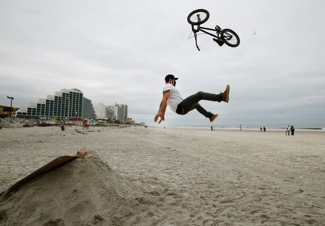 A beachgoer launches himself and his bike into the air while attempting to make a jump  hidden treasures on the beach in Daytona Beach, Sunday, Jan 3, 2021.