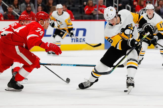 Pittsburgh Penguins defenseman John Marino (6) skates with the puck defended by Detroit Red Wings defenseman Madison Bowey (74) in the first period at Little Caesars Arena on Jan. 17, 2020.