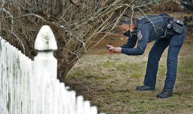 A Scituate officer snaps a photo of the firearm located by a K9.