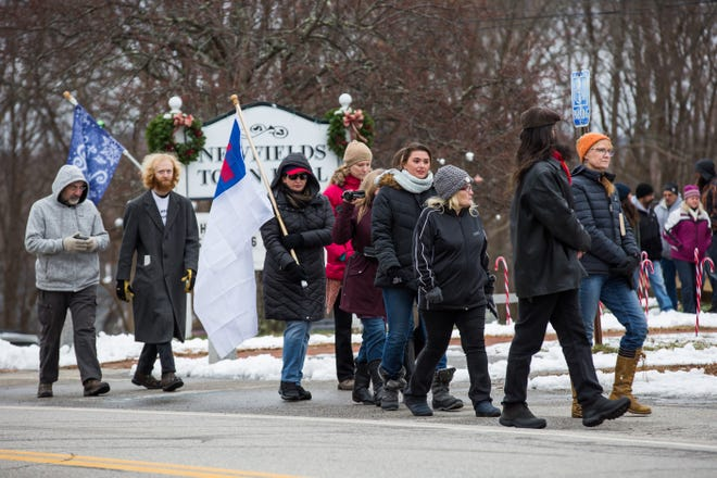 """A group of protesters, on Sunday, Jan. 3, march from the Newfields Town Hall to Gov. Chris Sununu's house to, in their words, """"end tyranny in the state of New Hampshire."""""""