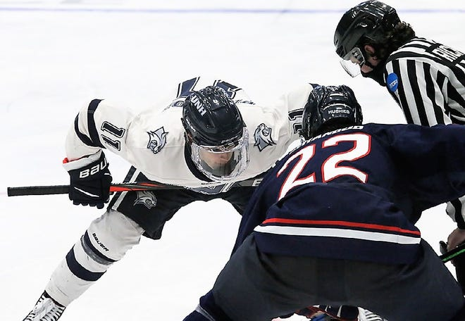 UNH's Jackson Pierson, left, squares off against Connecticut's Hudson Schandor on a faceoff during Friday's Hockey East game at the Whittemore Center. Pierson scored both goals in Saturday's 2-1 overtime win over UConn.