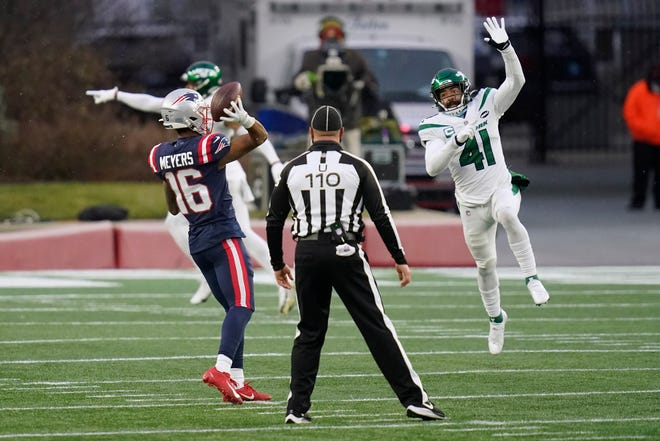 New England Patriots wide receiver Jakobi Meyers (left) throws a touchdown pass to quarterback Cam Newton while under pressure from New York Jets safety Matthias Farley in the second half of an NFL football game Sunday in Foxborough.