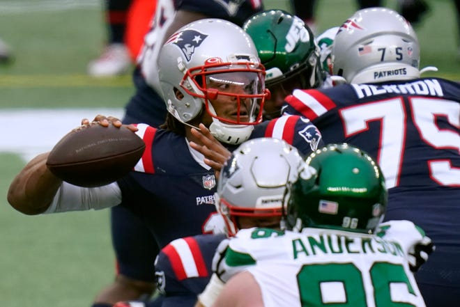 Patriots quarterback Cam Newton passes under pressure from Jets defensive end Henry Anderson in the first half of Sunday's season finale in Foxboro.