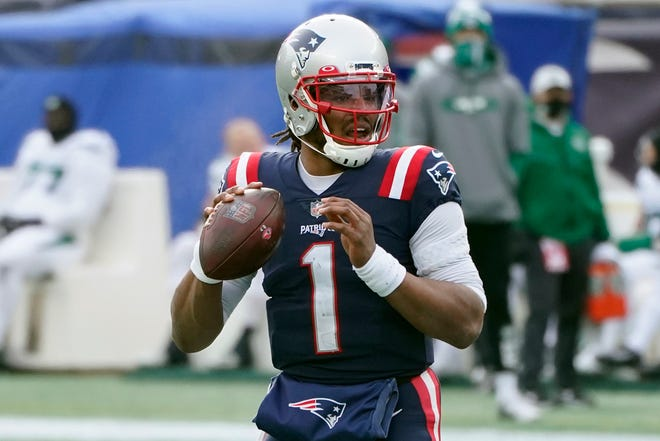 New England Patriots quarterback Cam Newton prepares to throw a touchdown pass to James White in the first half of the season finale against the New York Jets, Sunday, Jan. 3, 2021, in Foxborough.