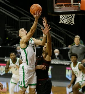 Oregon's Chris Duarte, center, goes to the basket for two of his 23 points in Saturday's win over Stanford.