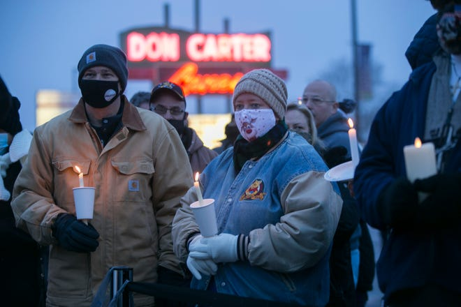 Gary and Stacy Mooney of Roscoe hold candles during a vigil at Don Carter Lanes on Saturday for the six victims of a shooting there on Saturday.