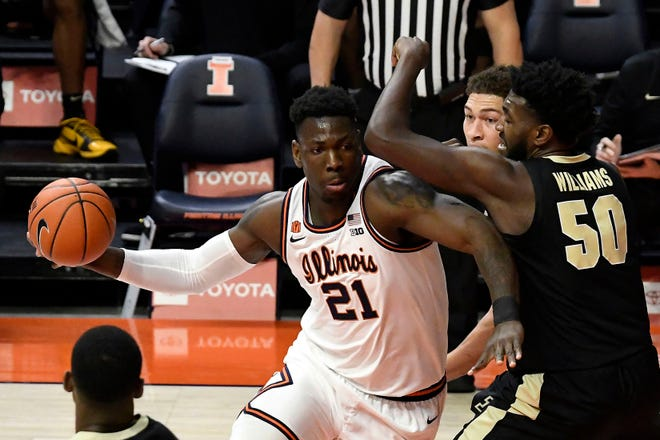 Illinois center Kofi Cockburn drives to the basket against Purdue forward Trevion Williams in the first half Saturday in Champaign. [HOLLY HART/THE ASSOCIATED PRESS]