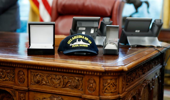 Some of the gifts given to President Donald Trump are seen on the Resolute Desk during a July 2017 Oval Office meeting with survivors of the attack on USS Arizona at Pearl Harbor.