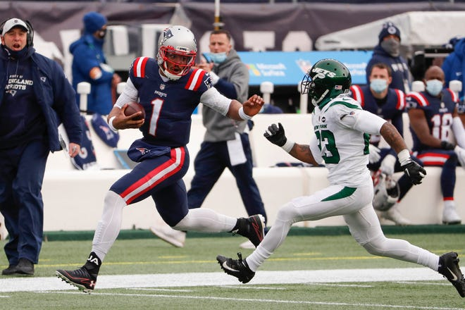 Patriots quarterback Cam Newton runs with the ball, with Jets cornerback Arthur Maulet in pursuit in the first half.