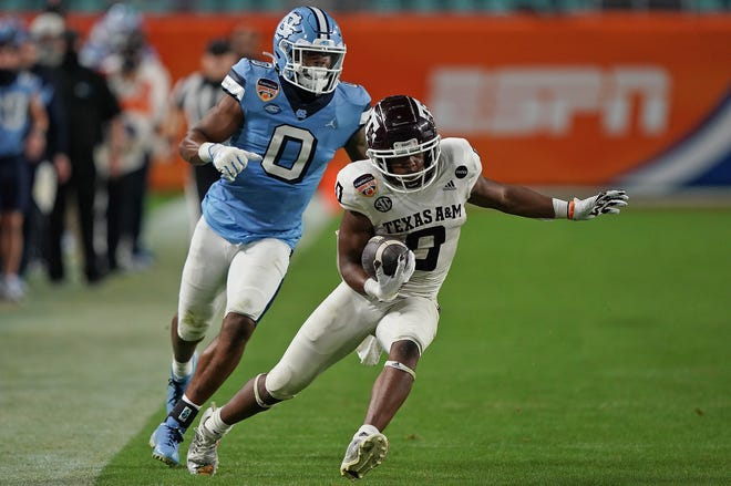 Texas A&M Aggies running back Ainias Smith has North Carolina defensive back Ja'Qurious Conley on the chase during the second half of the Orange Bowl.