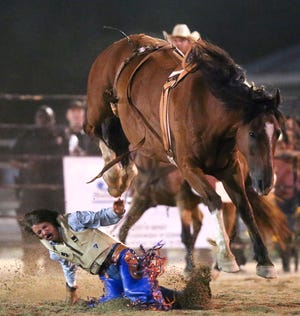 Nase Boswell hits the ground hard after being thrown during the bareback bronc riding competition from the horse Johnny Cash in the 11th annual Sokol Park Rodeo in the Ray C. Jenkins Multipurpose Arena Friday, July 17, 2020. [Staff Photo/Gary Cosby Jr.]