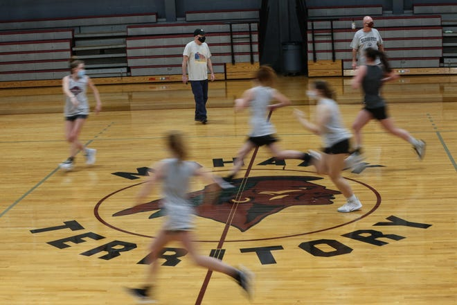 Girls run down the court over the Mohawk logo at center court during girls varsity basketball practice at Millis High School, Jan. 2. The image is among native symbols the school committee has formally voted to remove from school facilities and athletic gear.