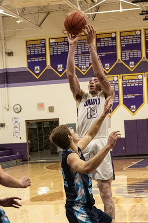 Unioto freshman Tayvion Galloway shoots over Adena's Preston Sykes during a battle for SVC dominance on Jan. 2, 2021. Unioto defeated Adena 55-45 with Galloway securing 15 of those points for Unioto.