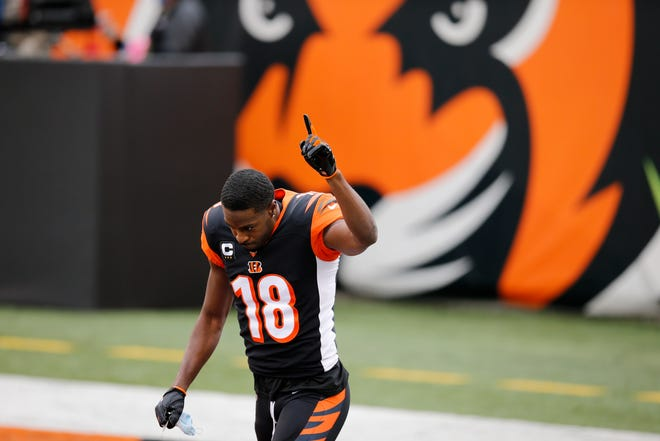 Cincinnati Bengals wide receiver A.J. Green (18) raises a hand as he's introduced for what might be his final game with the team before the first quarter of the NFL Week 17 game between the Cincinnati Bengals and the Baltimore Ravens at Paul Brown Stadium in downtown Cincinnati on Sunday, Jan. 3, 2021. The Ravens led 17-3 at half time.
