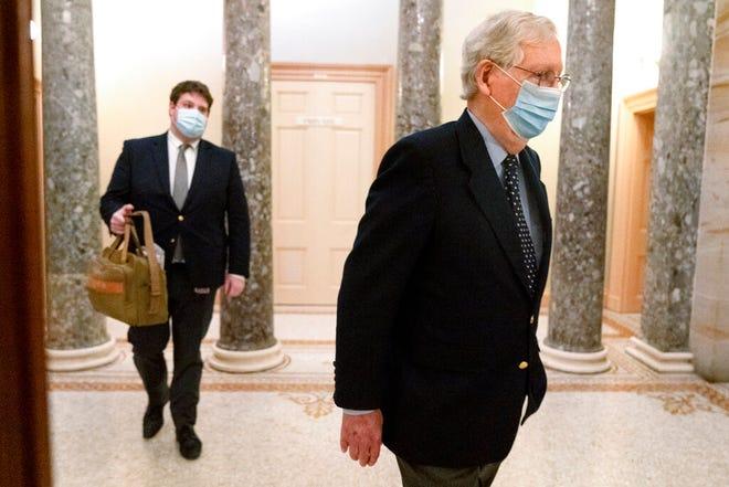 Diikuti oleh seorang staf yang memegang tas, Pemimpin Mayoritas Senat Mitch McConnell dari Ky., Kanan, meninggalkan Capitol untuk hari itu, Selasa, 29 Desember 2020, di Capitol Hill di Washington. (Foto AP / Jacquelyn Martin)