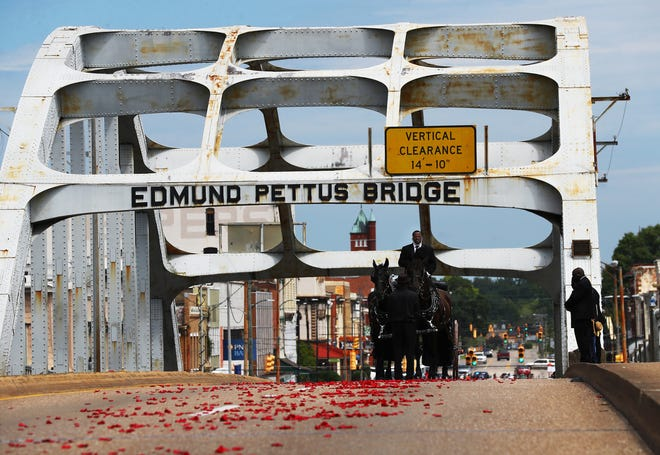 The body of Rep. John Lewis pauses at the top of the bridge for one minute while making the final crossing over the Edmund Pettus Bridge, site of the historic 1965 voting rights marches, while family members at right look on Sunday, July 26, 2020 in Selma, Alabama. The congressman from Georgia and civil rights icon died July 17, 2020, at age 80 after a battle with pancreatic cancer. (Curtis Compton/Atlanta Journal-Constitution/TNS)