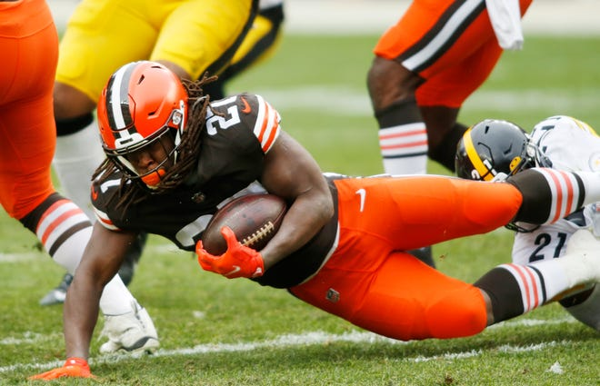 Browns running back Kareem Hunt (27) gets tackled by Pittsburgh Steelers free safety Sean Davis (21) during the first quarter of the Browns' 24-22 playoff-clinching win Sunday at FirstEnergy Stadium. [Associated Press]