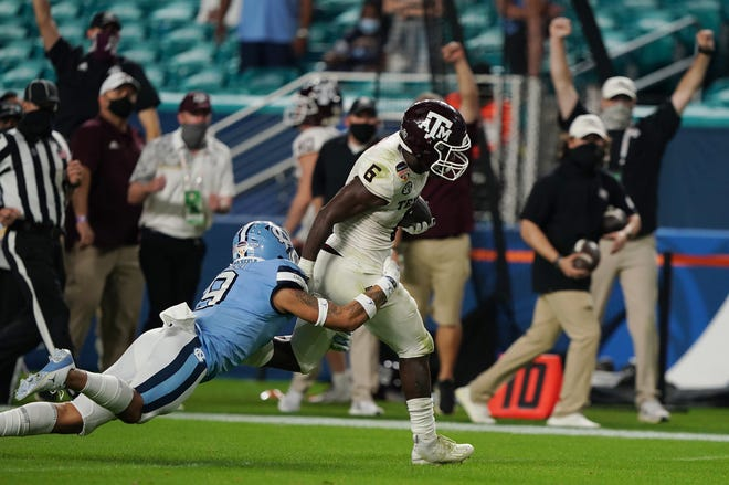 Texas A&M running back Devon Achane runs past North Carolina defensive back Cam'Ron Kelly for a 76-yard touchdown during the the Aggies' 41-27 win in the Orange Bowl Saturday. Achane was named the game's MVP after rushing for 140 yards in the victory.