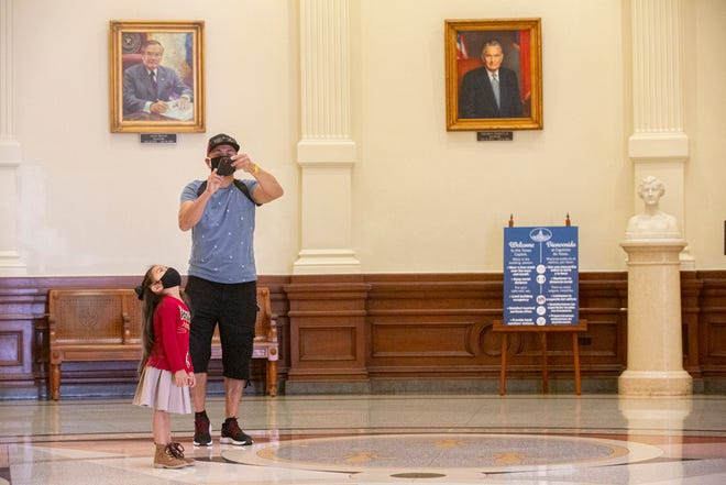 Carlos Curiel of San Diego, California, takes a picture of his daughter Rebecca, 5, as she looks up at the ceiling of the Capitol in Austin on Monday, Jan. 4, 2021. After having been closed to the public since March of last year, the Capitol has finally opened its doors to visitors.