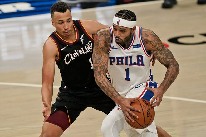 Philadelphia 76ers guard Mike Scott, right, drives against Cavaliers guard Dante Exum during a recent game. Exum has been a strong defensive presence in the absence of first-round pick Isaac Okoro. [Tony Dejak/Associated Press]
