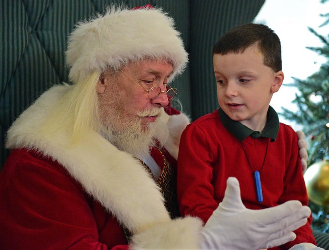 Aiden Jackson 6, of of Akron talks with Santa (Gilbert Kiper) at the Summit Mall during a Autism Society event in 2015. (David Dermer/Special to the Akron Beacon Journal)