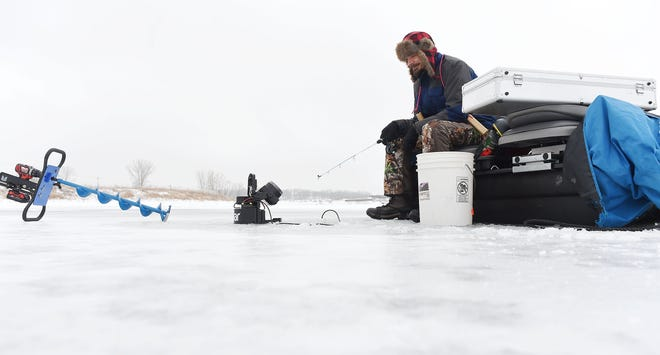 Ben Tompkins of Ames waits for a bite after he dropped a line through the ice of the frozen Ada Hayden Park while ice fishing Monday, Jan. 4, 2021, in Ames, Iowa.
