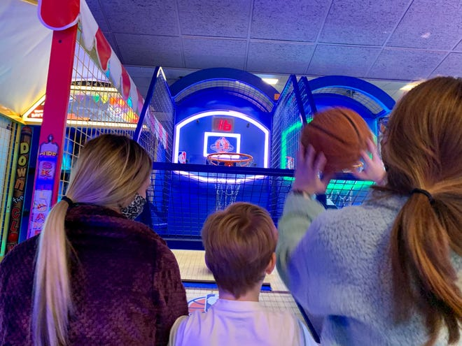 The Crooks family plays basketball at the Putt Putt Fun Center in Augusta in early January. Among its safety steps, it offers sanitation supplies for guests who prefer to clean the arcade machines themselves.