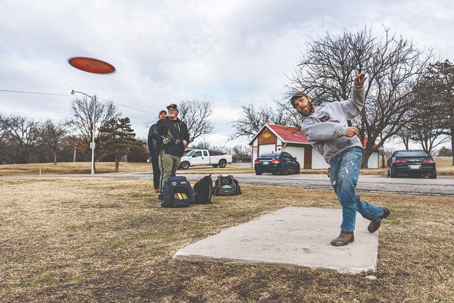 Kirk Johnson and Caden Crocker watch as Brandon Stafford tees off the No. 4 pad with a forehand drive on Wednesday, Dec 30, at the Sooner Park disc golf course in Bartlesville.