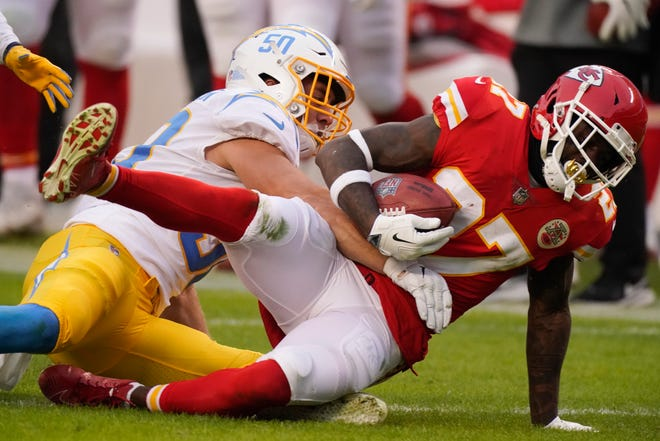 Kansas City Chiefs' Rashad Fenton (27) is tackled by Los Angeles Chargers' Cole Christiansen, left, during a game Sunday in Kansas City.