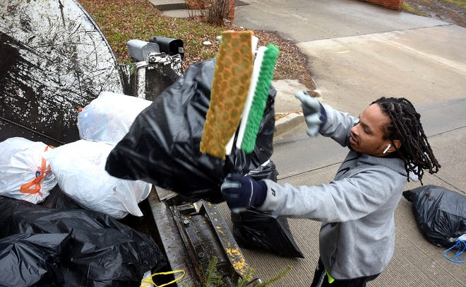 City employee Marquez Dampier loads trash into a truck Monday on Scott Boulevard. Beginning Feb. 1, all trash placed on the curb for collection must be in city-provided trash bags with city logos.