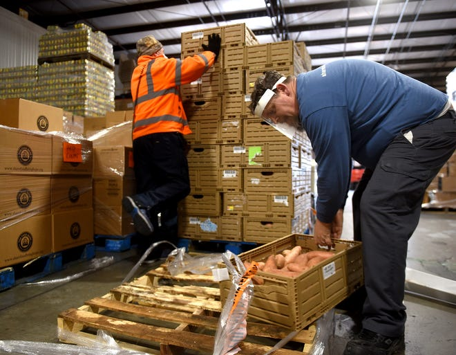 Food Bank for Central & Northeast Missouri warehouse supervisor Dave Beckman, left, and warehouse driver Joe Lewis load sweet potatoes onto a forklift Monday. Donors to CoMo Gives provided $91,365 to the food bank for 2020.