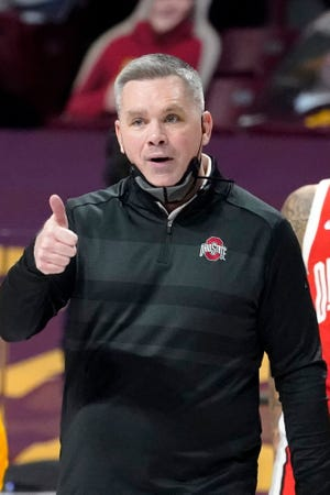 Ohio State head coach Chris Holtmann has a word with one of his players in the second half of an NCAA college basketball game against Minnesota, Sunday, Jan. 3, 2021, in Minneapolis.
