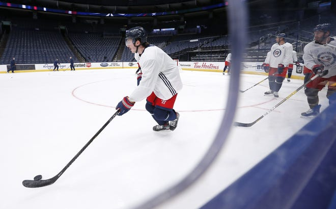 Blue Jackets defenseman Zach Werenski skates with the puck during Monday's training camp session at Nationwide Arena.