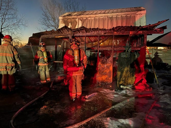 Fire crews assess the damages caused by the shed fire Sunday morning.