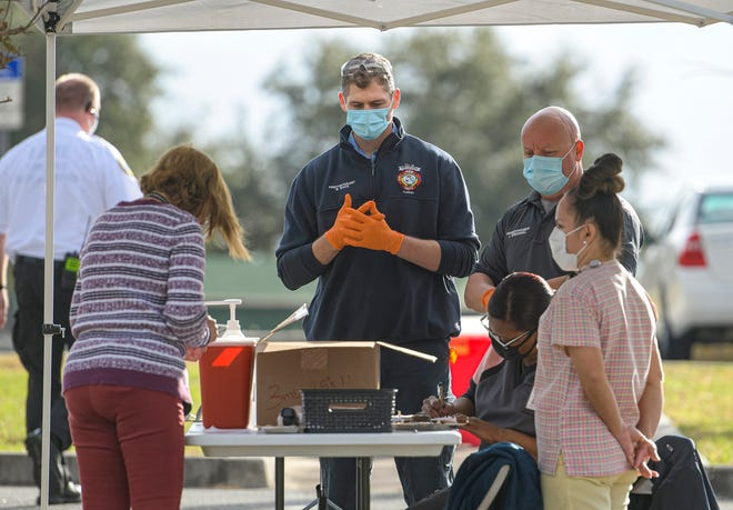 Health care workers collect patient information at a COVID-19 vaccine distribution site at Cooper Memorial Library in Clermont on Wednesday, Dec. 30, 2020. [PAUL RYAN / CORRESPONDENT]