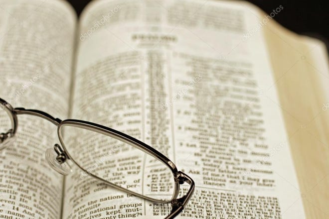 Glasses are seen on top of Bible during a Bible study class.