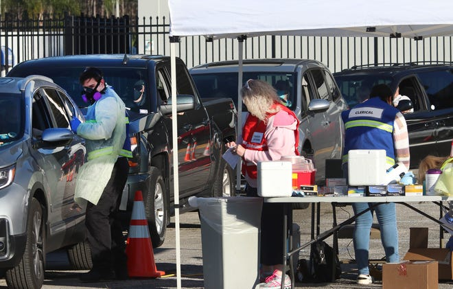 Health care professionals administer the Covid-19 vaccine in the Municipal Stadium parking lot, Monday January 4, 2021 in Daytona Beach.