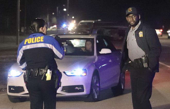 Daytona Beach Police Chief Jakari Young, right, oversees traffic backed up on LPGA Boulevard, as officers keep the line moving into the Municipal Stadium parking lot on Monday, Jan. 4, 2021. The stadium was the site of  the first  COVID-19 vaccine to be administered to the general public in Volusia County.