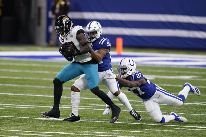 Jaguars wide receiver Chris Conley (18) is tackled by the Colts' Anthony Walker (54) and Xavier Rhodes (27) during the first half.